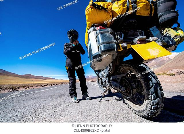 Woman standing next to touring motorbike on gravel road, Uyuni, Oruro, Bolivia, South America