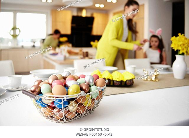 Easter eggs in basket on table at home with mother and daughter in background