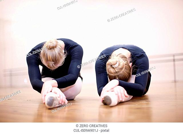 Two ballerinas in pose on studio floor
