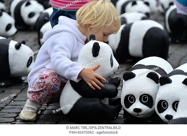 Three-year-old Yuna holds a Panda sculpture made of papier-mache at the Cathedral Square in Erfurt, Germany, 11 September 2013