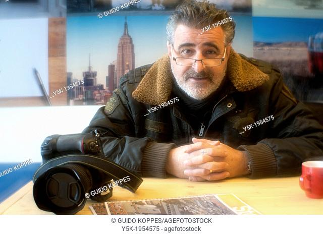 Breda, Netherlands. Middle aged male photographer and photo journalist sitting at an office table, while having a conversation