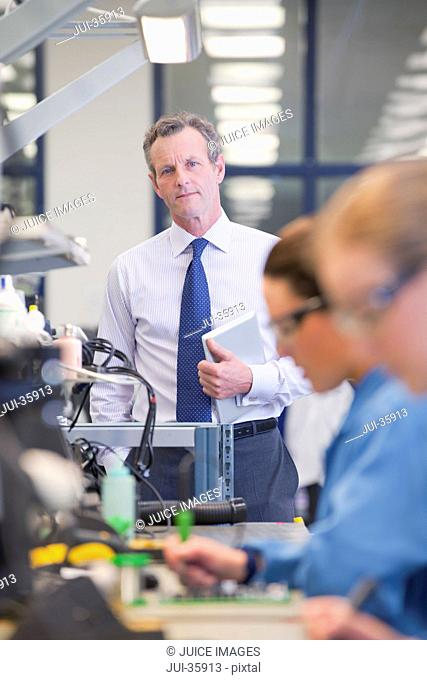 man soldering circuit board stock photos and images age fotostockportrait of businessman with digital tablet at production line in circuit board manufacturing plant