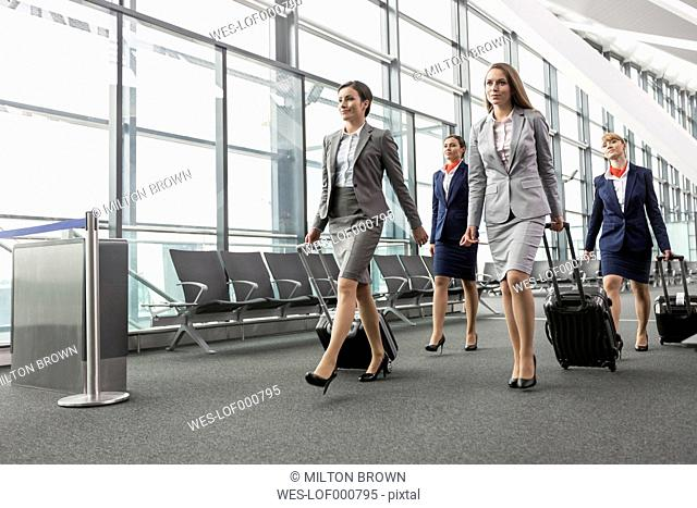 Businesswomen and flight attendants walking at the airport