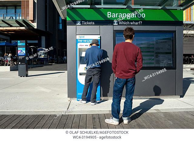 Sydney, New South Wales, Australia - A man is buying a ferry ticket at a ticket machine on Wulugul Walk in Barangaroo South