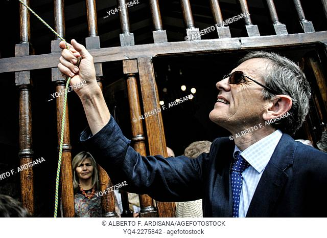 A man rings the bell of the church during the procession of Lledías. Llanes, Asturias, Spain