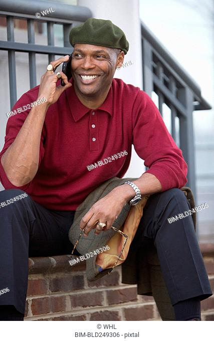 African American man sitting on stoop talking on cell phone