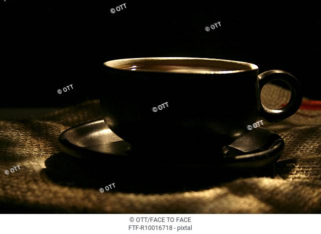 Cup of coffee is placed on jute mat in a dark area