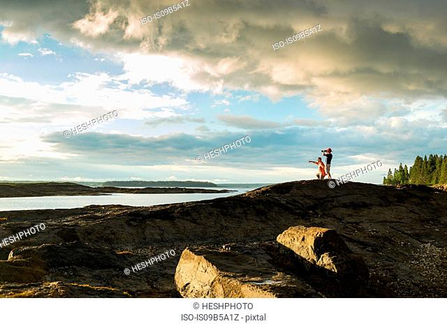 Distant view of senior man and son looking through binoculars at coast of Maine, USA