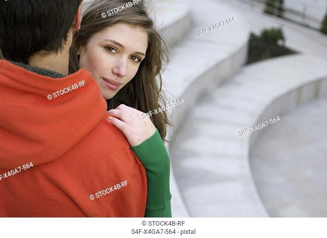 Young couple embracing each other, woman looking at camera