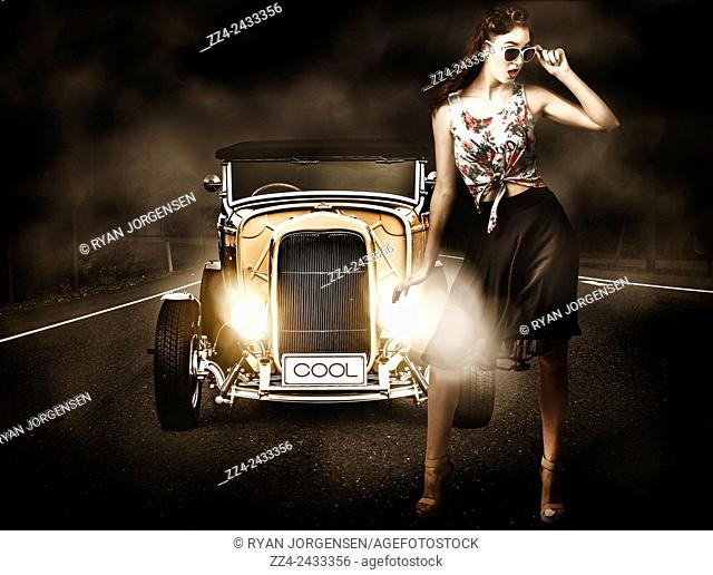 Fashion photography of a beautiful brunette girl in upmarket fashion apparel standing beside cool yellow hotrod car. Stopping traffic and turning heads