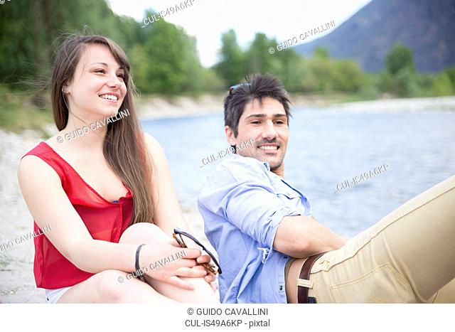 Young couple sitting by river