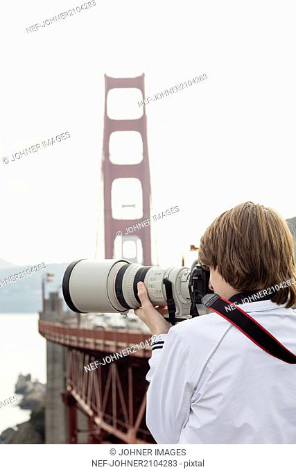Boy taking picture, Golden Gate Bridge on background