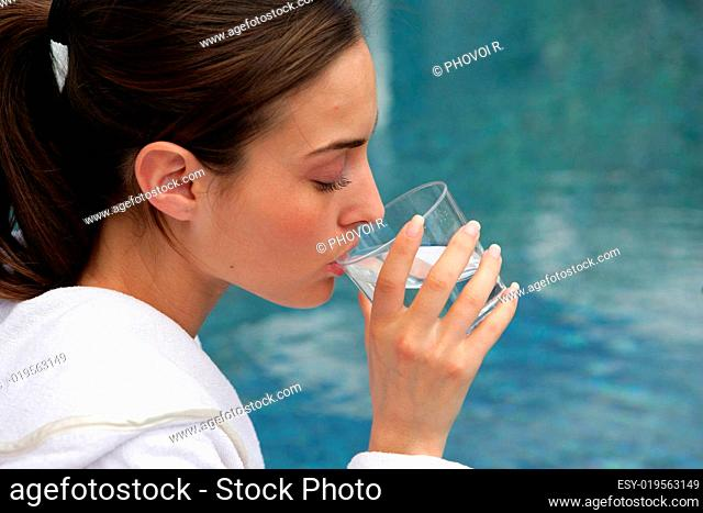 Young woman in bathrobe drinking a glass of water