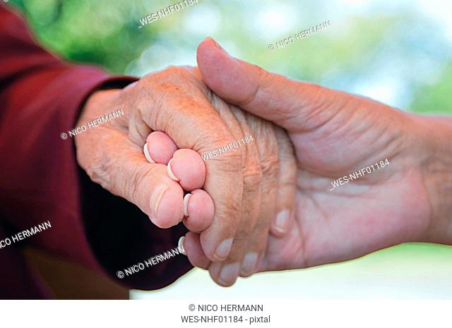 Senior women holding hands, close-up