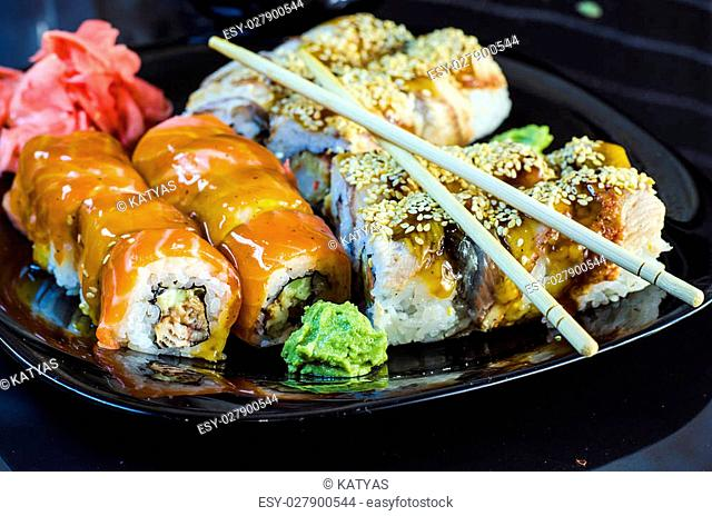 variety of sushi rolls on a black bowl with chopsticks