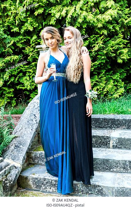 Teenage girls wearing prom dresses holding champagne flute looking at camera smiling