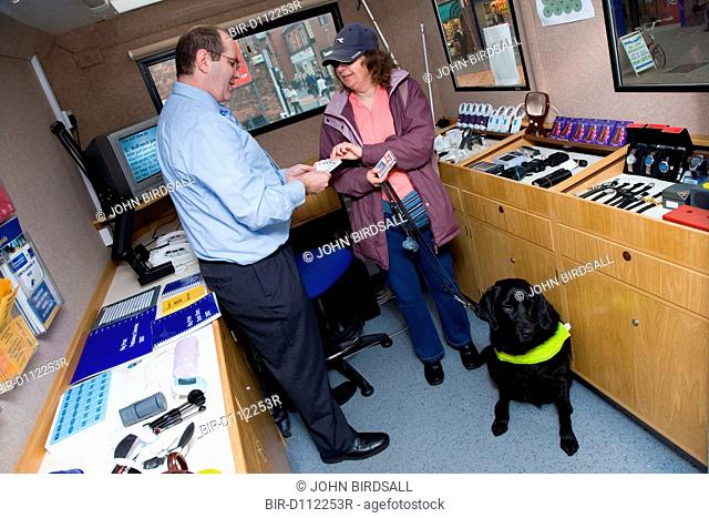 Resource Officer advising a woman with severe sight impairment who is visiting the mobile resource unit
