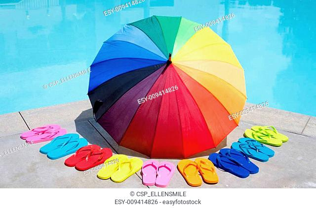 Color umbrella and flip flops by the pool
