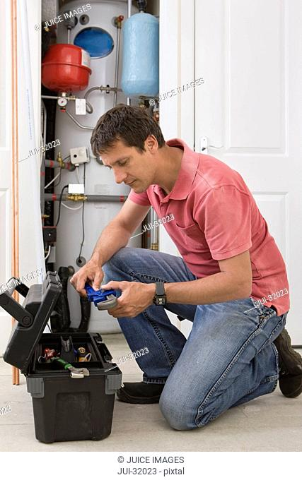 Handyman with wrench kneeling before toolbox in front of boiler in closet