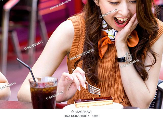 Business woman eating a cake at an outdoor cafe