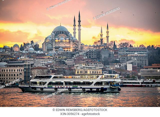 As the sunsets, a ferry boat glides across the waters of the Golden Horn with the Suleymaniye Mosque and the city of Istanbul, Turkey in the background