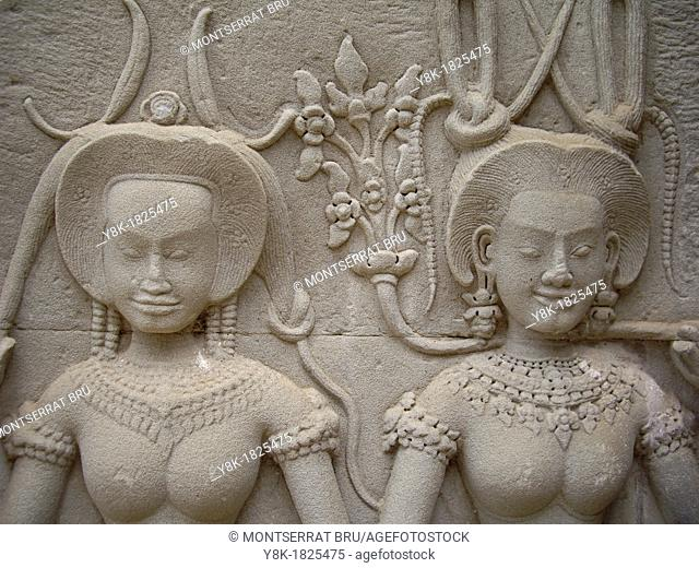 Stone carved female faces with earrings, hairband and collar, Angkor Wat, Cambodia