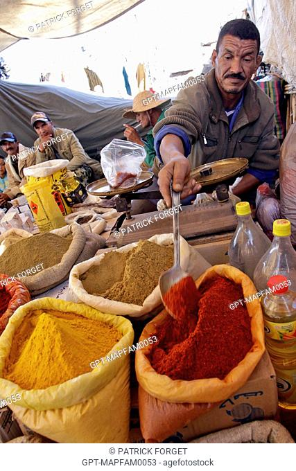 A SELLER OF COLORFUL SPICES IN THE BERBER MARKET OF TAHANAOUTE, AL HAOUZ, MOROCCO
