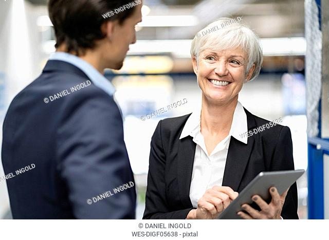 Smiling businessman and senior businesswoman with tablet talking in a factory