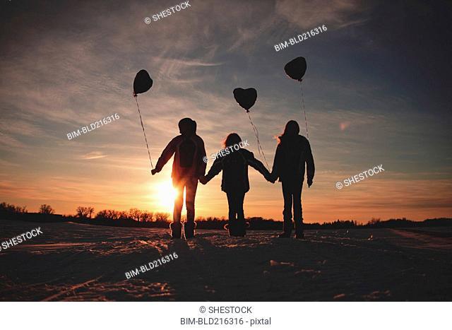 Caucasian girls walking with balloons at sunset