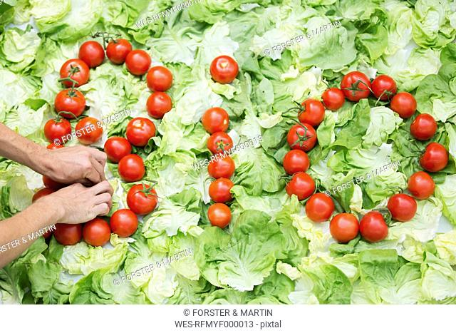 Germany, Human hand forming bio letters with tomatoes on cabbage leaf