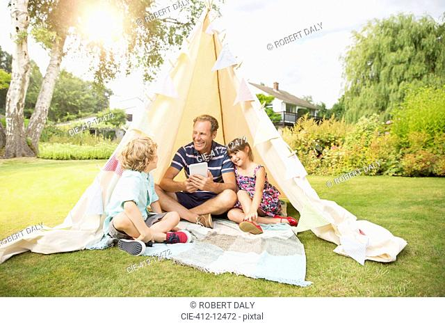 Father and children relaxing in teepee in backyard