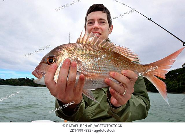 A man holds a fish that he caught during fishing at sea on a fishing boat