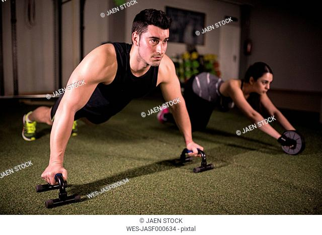 Man and woman doing crossfit exercises in gym