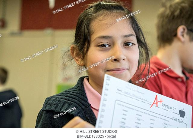 Hispanic student showing grade in classroom