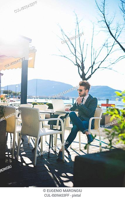 Businessman using laptop at lakeside cafe, Rovato, Brescia, Italy