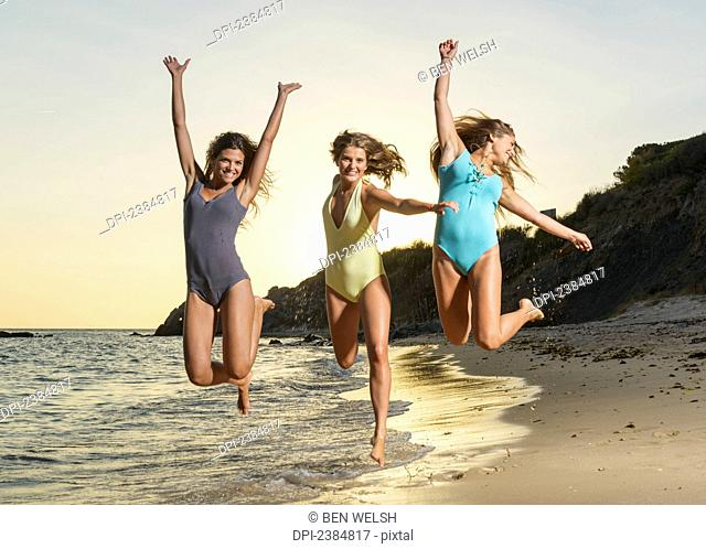Three young women in bathing suits jumping in mid-air together on the beach; Tarifa, Cadiz, Andalusia, Spain