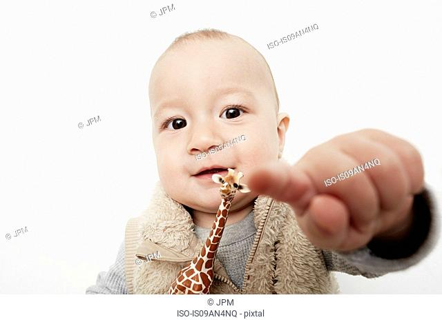 Portrait of cute baby boy pointing finger at camera