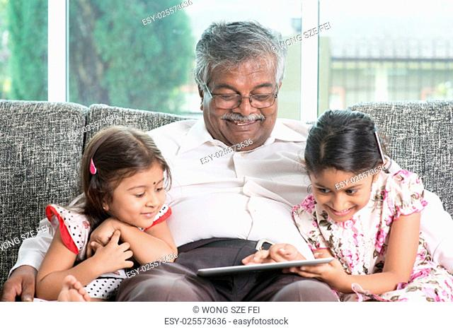 Modern technology concept. Grandparent and grandchildren using touch screen tablet computer. Portrait Indian family at home