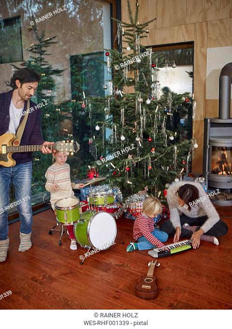 Family playing music together under Christmas tree
