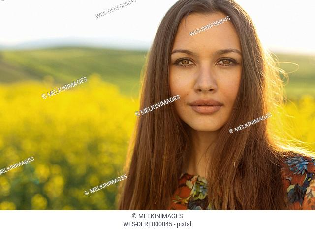 Portrait of young woman with brown hair and brown eyes in nature