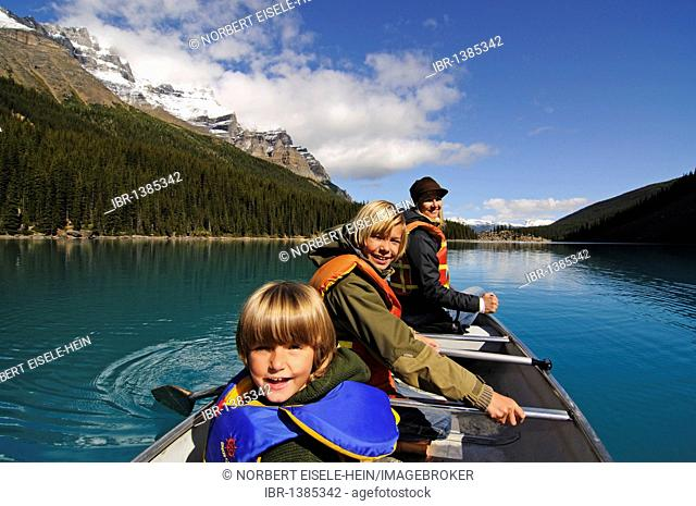 Woman and children in a canoe, Moraine Lake, Banff National Park, Alberta, Canada
