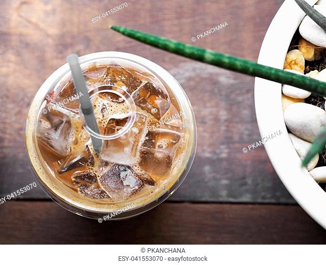 Close up take away transparent plastic glass of ice latte coffee with straw near flowerpot on wooden table in coffee shop. Top view