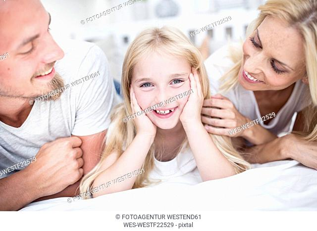 Portait of smiling girl with parents in bed