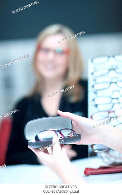 Shop assistant showing customer glasses in opticians shop