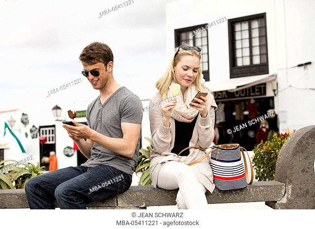 young couple with mobile phones, eating ice cream