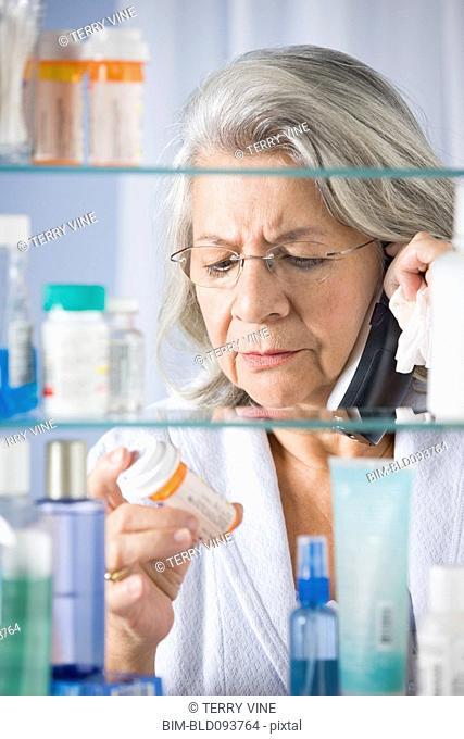 Hispanic woman talking on phone checking prescription