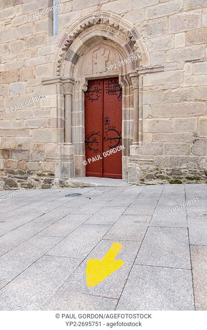 Galicia, Spain: Typical yellow arrow marking the Camino Francés on the Rúa Maior near the Iglesia San Salvador. Many pilgrims choose Sarria as the starting...