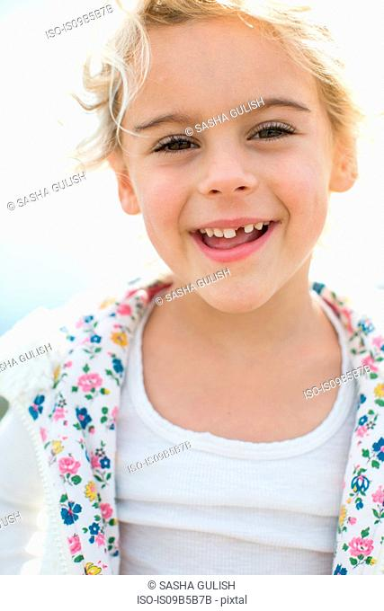 Portrait of cute blond girl with tooth missing at coast