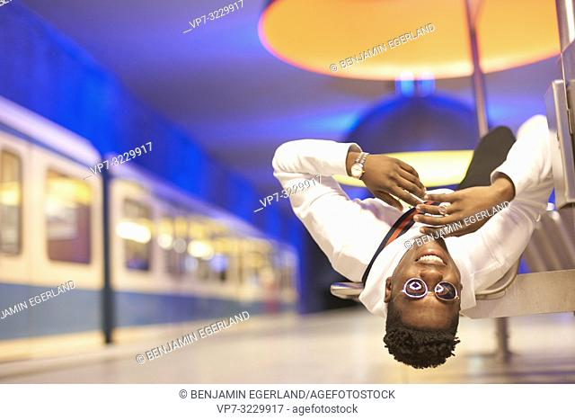 young man laying upside down on bench in underground train station, public transportation, in Munich, Germany