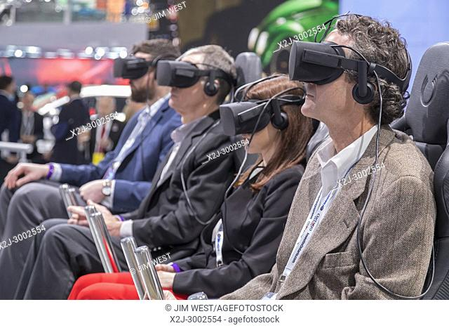 """Detroit, Michigan - People take a virtual reality ride through the """"""""City of Tomorrow"""""""" at Ford's Future Mobility VR Experience during the North American..."""